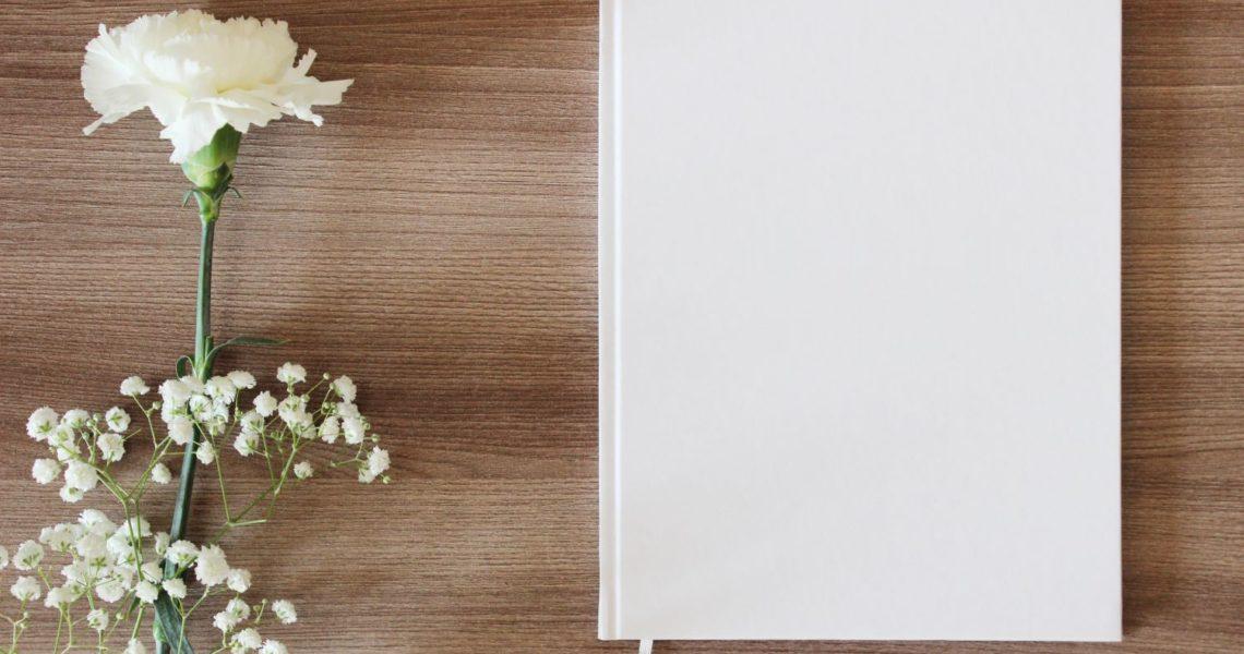 biała okładka i biały kwiat na drewnianym stole