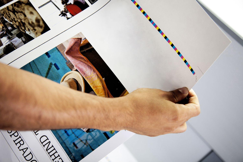 mężczyzna trzymający kolorowy wydruk