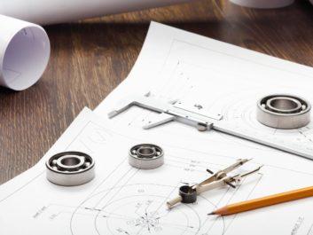 cyrkiel, ołówek i projekty leżące na biurku